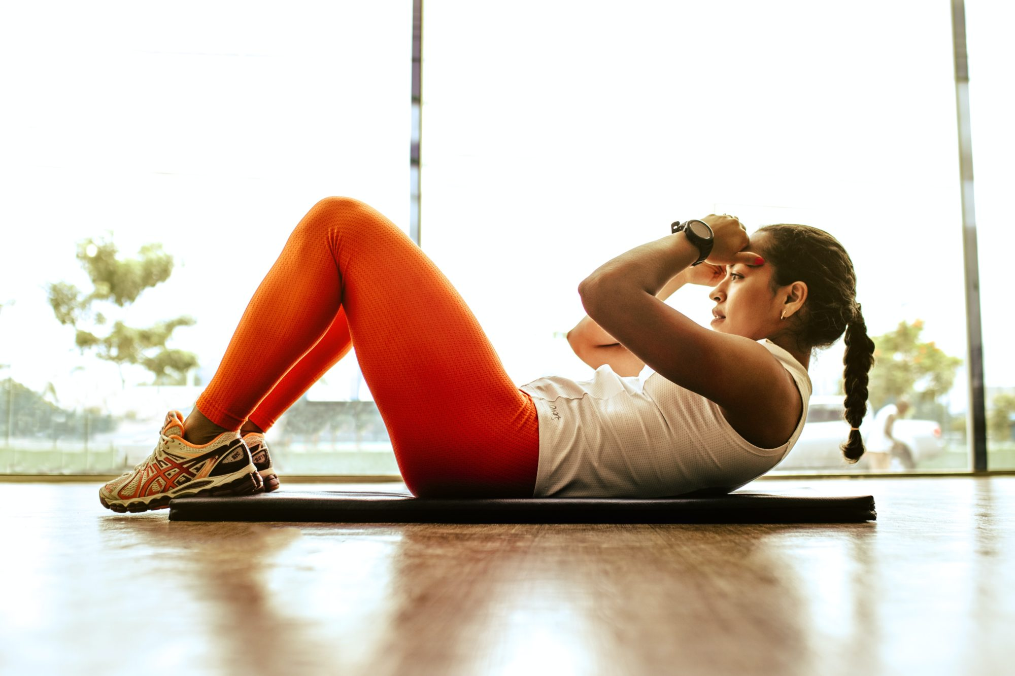 Woman in workout clothes doing sit ups