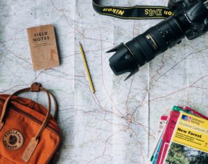 world map with a camera, backpack, and travel brochures on it