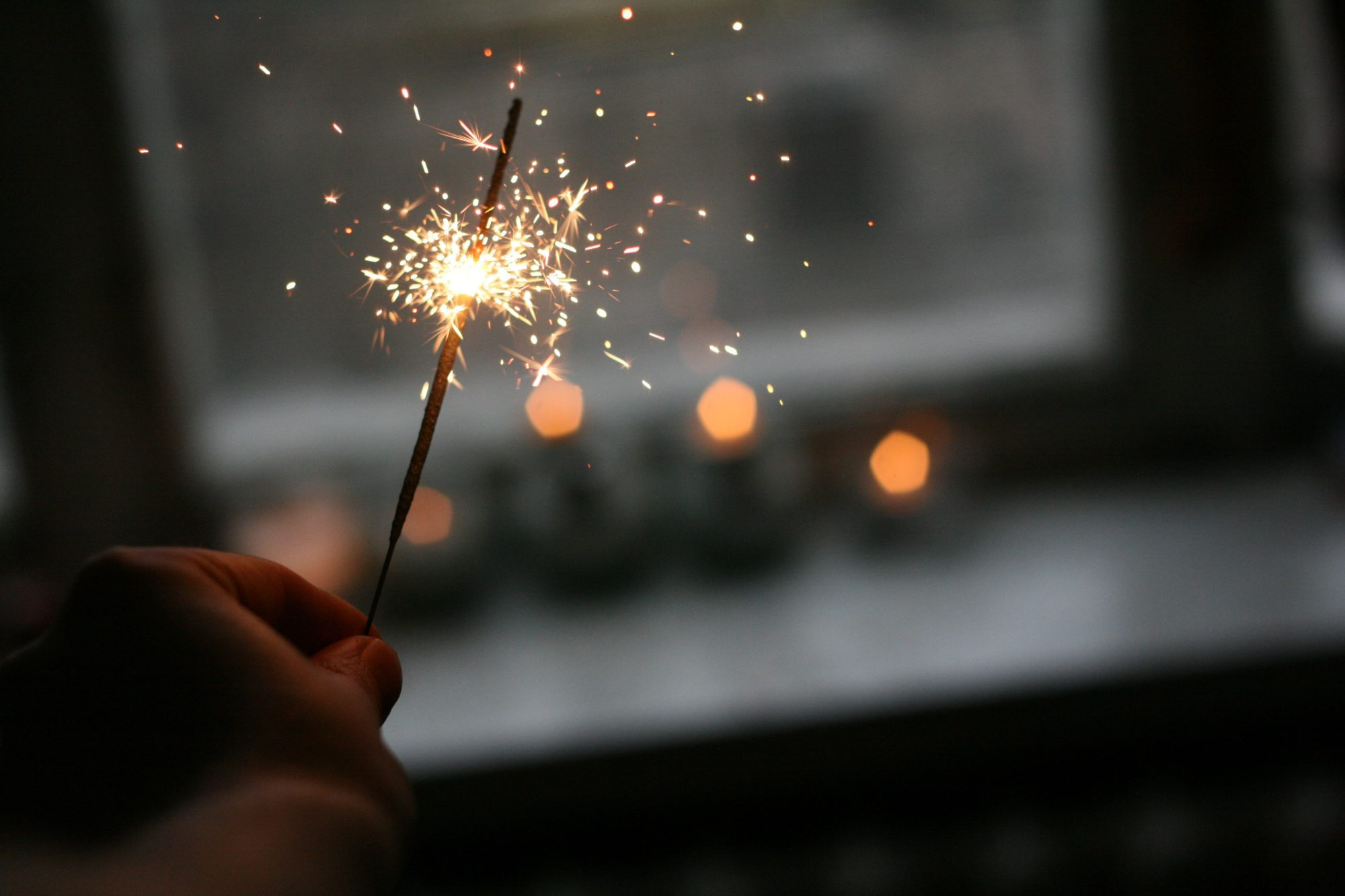 Person's hand holding a sparkler that is lit and sparkling
