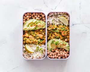 Two meal prep boxes filled with chick peas, avocados, rice, lemon, chicken and corn