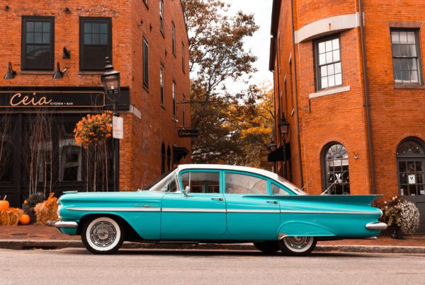 teal colored classic car parked infront of two orange urban buildings