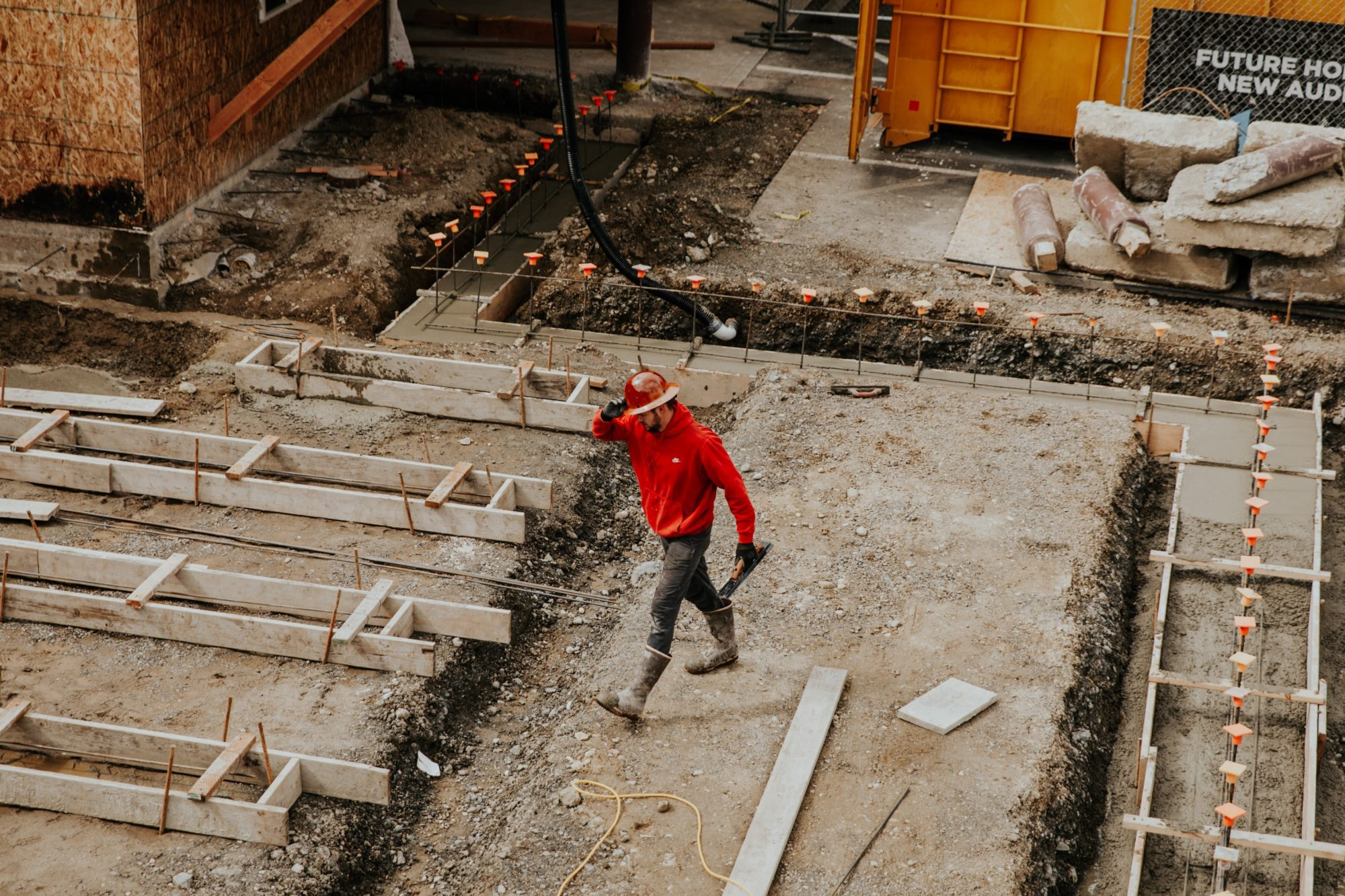 man in red hoodie with a construction hard hat on walking through construction site
