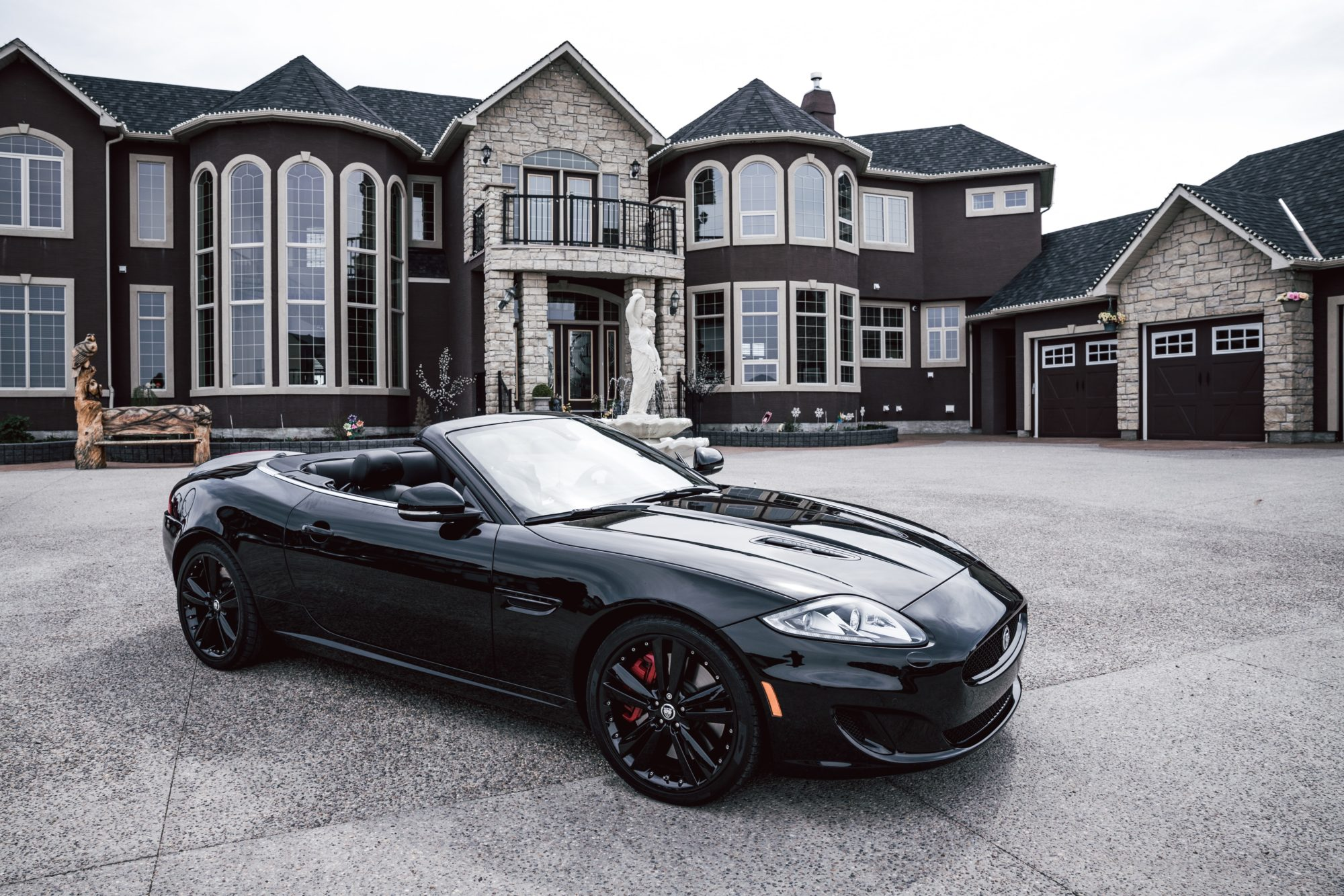 black sports car in front of mansion