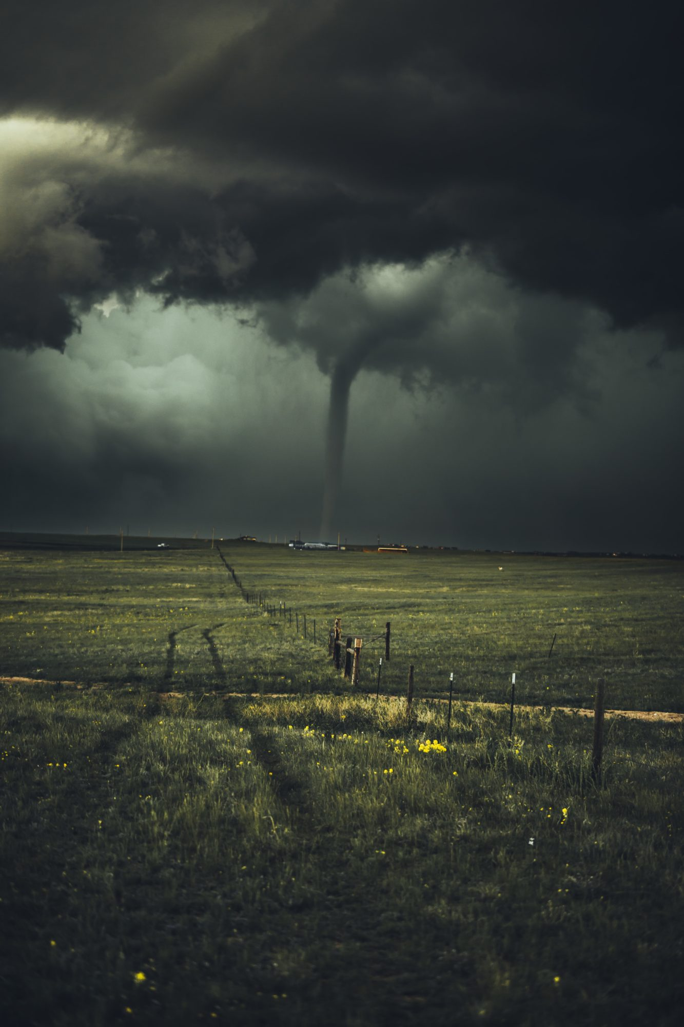 Tornado hitting land in a green field