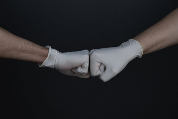 fist bumping with gloves due to covid