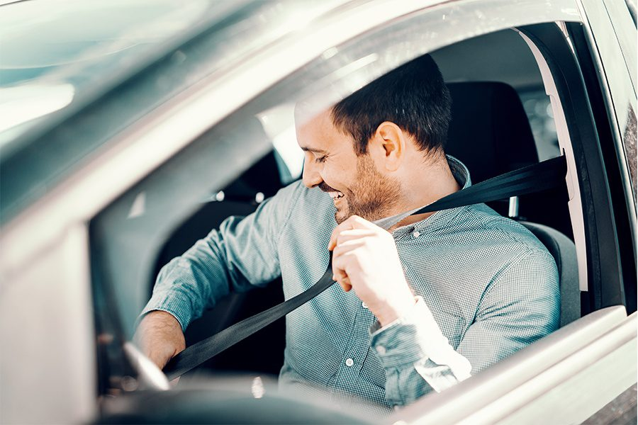 ERIE YourTurn Rewards Program - Closeup of a Man Practicing Safe Driving by Fastening His Seatbelt in His Car