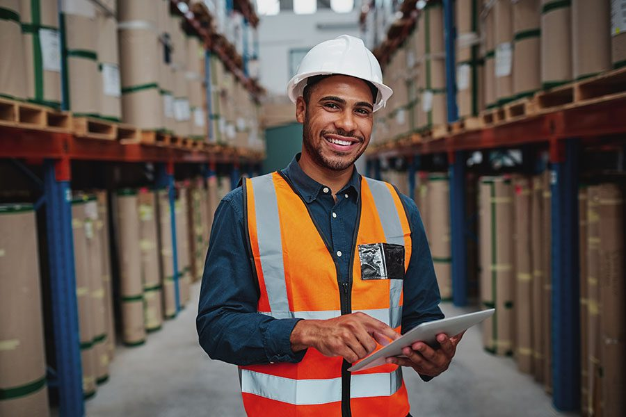 Warehousing and Logistics Insurance - Portrait of Smiling Warehouse Manager Using a Digital Tablet in a Warehouse While Standing between Shelves and Looking at the Camera