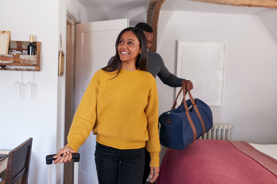 Short-Term Rental Insurance - Smiling Young Couple Opening the Door to a Vacation Rental and Carrying Luggage While Spending the Weekend Away From Home