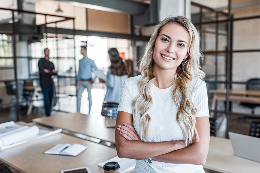Business Insurance - Portrait of Woman in the Office with Background and Coworkers Blurred