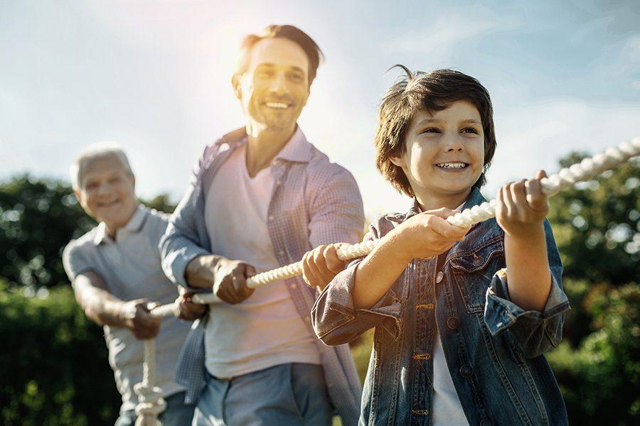 Employee Benefits - Smiling Son Dad and Grandfather Standing One by One While playing Tug of War