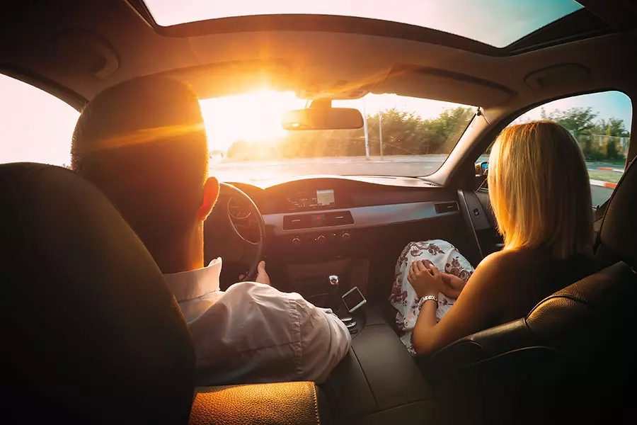 Its Your Turn to Earn Rewards - Husband and Wife Sitting in the Front Seat of a Car Driving into the Sun