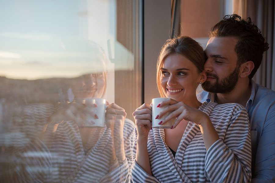 Personal Insurance - Young Couple at Home Looking Out Window