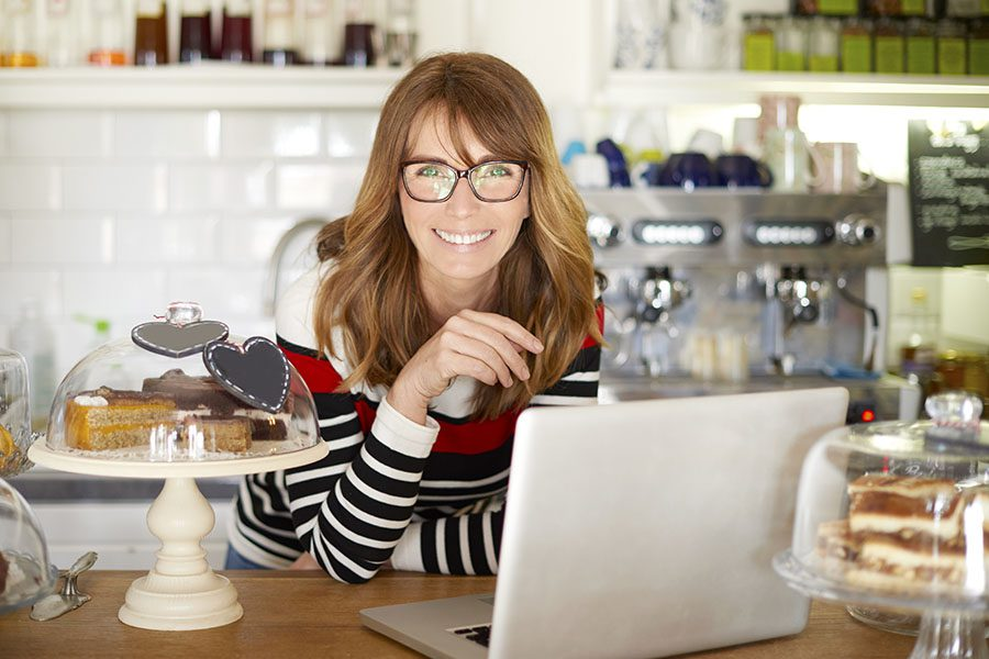 Business Insurance - Portrait Of Small Coffee Shop Business Owner With Her Laptop