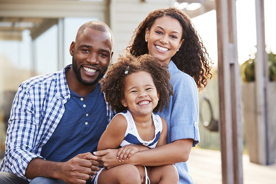 Personal Insurance - Portrait Of Family With Daughter Standing Outside Their Home