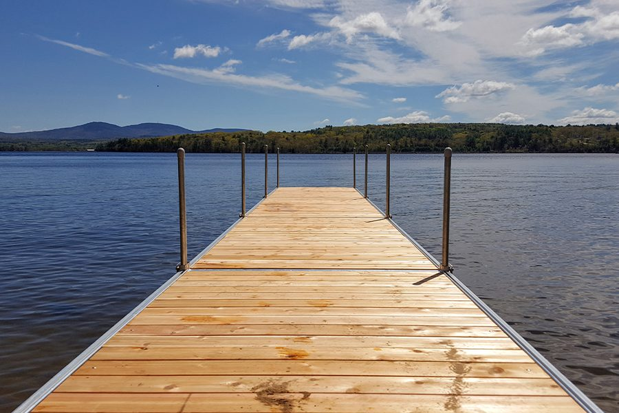 Laconia, NH - View of Dock at a Lake in Laconia, New Hampshire on a Sunny Day