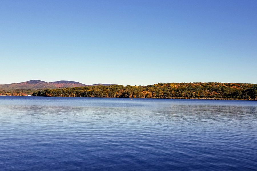 New Hampshire - Landscape View of Lake and Hills and Trees in Laconia, New Hampshire at Dusk