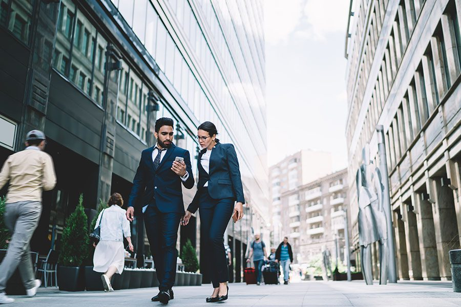 About Our Agency - Two People in Business Suits Walking Down Busy City Street