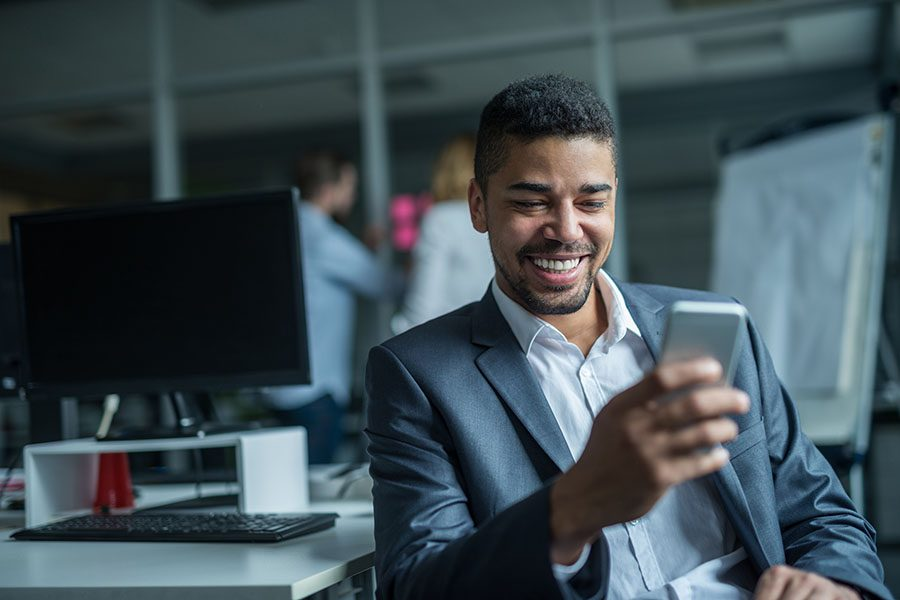 Contact - Man In Suit Smiling at His Phone