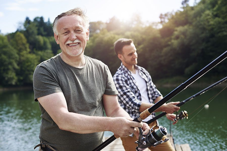 Personal Insurance - Older Man Fishing With Grown Son On A Sunny Day