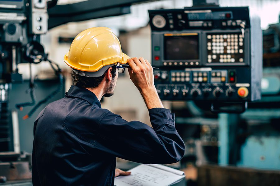 Specialized Business Insurance - Worker in Hard Hat Checks Equipment In A Manufacturing Plant