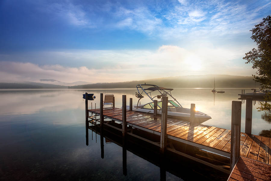 Smithville, MO Insurance - Boat Anchored to a Small Wooden Dock on a Calm Lake at Sunrise With Mist Rising Over the Water