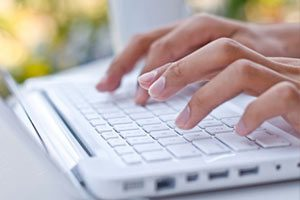 Close View of Woman's Hands Typing on a White Laptop