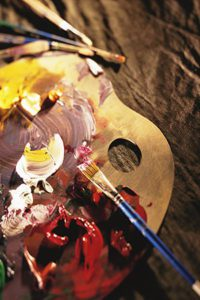 Artist's Paint Palette With Red, White and Yellow Paint Swirled Together, With Paint Brushes Resting Nearby