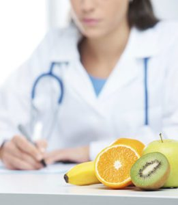 Doctor in a White Lab Coat and Stethoscope Writes on a Notepad at Her White Desk With Cut Fruit Sitting in Front of Her