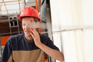 Construction Worker in a Red Hardhat With a Serious Head Wound Grimaces in Pain and Leans Against the Wall of a Construction Site