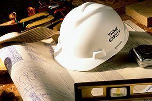 White Hard Hat Reading 'Think Safety' Sits on Top of Construction Blueprints