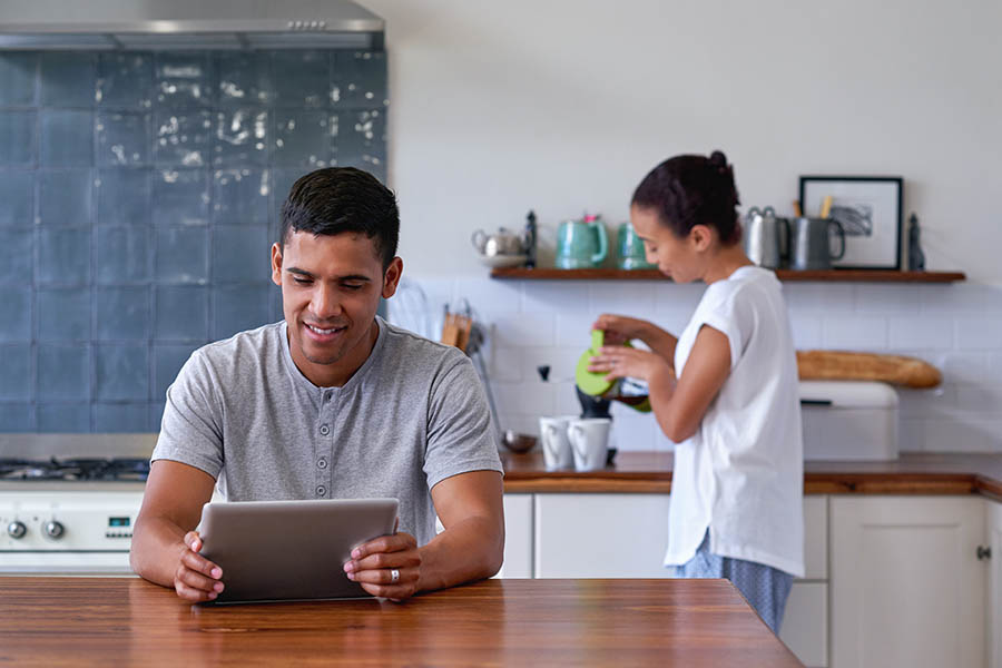 Blog - Couple Relaxing in Kitchen, Wife Pouring Coffee While Husband Reads Tablet at the Kitchen Island
