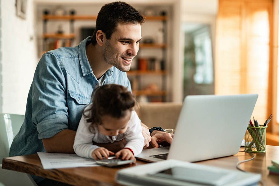 Client Center - Father Smiles and Uses Laptop at Desk While Infant Daughter Plays With Calculator in His Lap