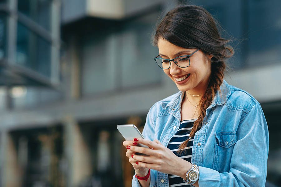 Contact Us - Young Woman in Denim Shirt and Glasses Smiles on a City Street, Making a Call on Her Smartphone