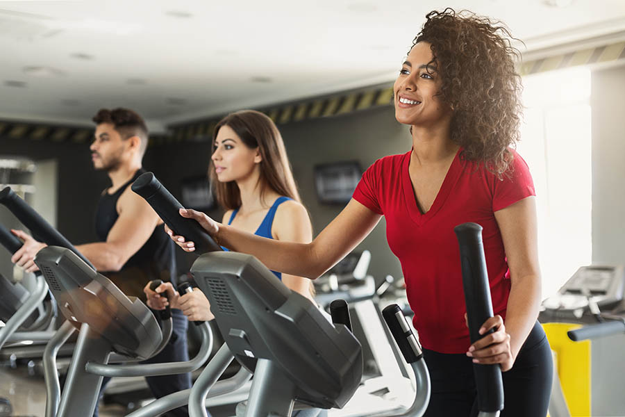 Employee Benefits - Young Woman and Coworkers Smiles and Uses Eliptical Machine in a Gym