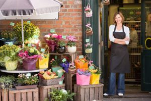 Florist in Black Apron Poses Outside Her Brick Flower Shop, Plants Arranged on Crates Under an Umbrella Outside the Shop
