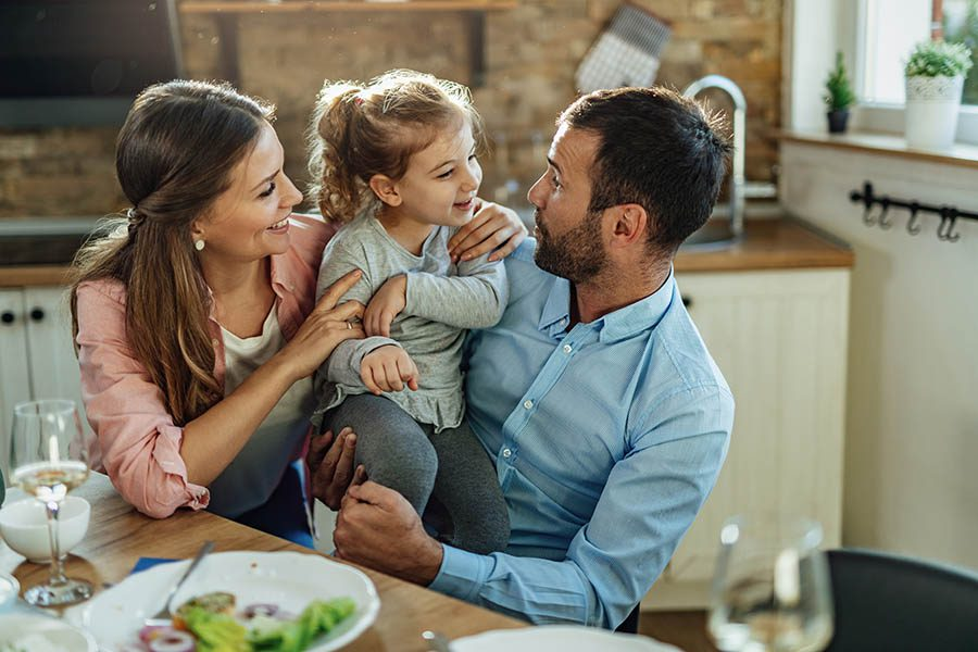 Personal Insurance - Well-Dressed Family Enjoying Dinner in Their Kitchen, Toddler Daughter Sitting in Dad's Lap