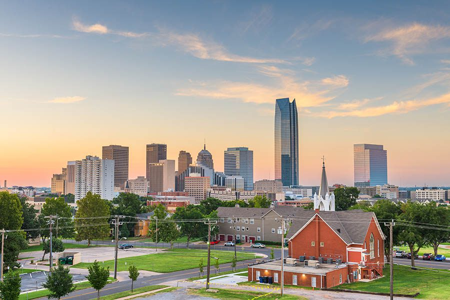 Piedmont, OK Insurance - Skyline of Oklahoma City Shines at Sunset, Seen From a Suburban Neighborhood With Homes and Churches in the Foreground