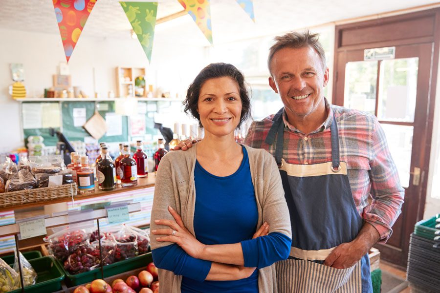 Business Insurance - Shop Owners in Front of an Organic Fruit Stand