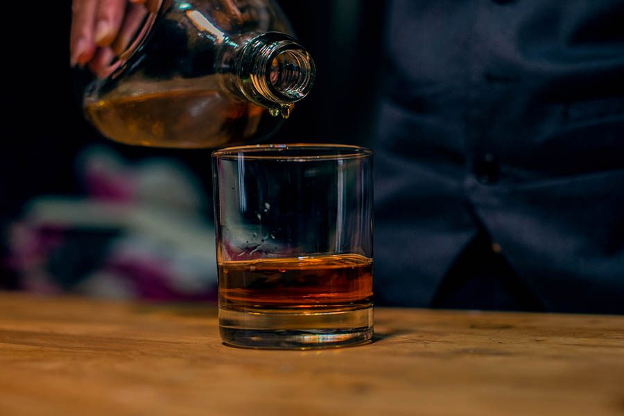 Distillery Insurance - Glass of Bourban Flowing into a Glass at a Bar