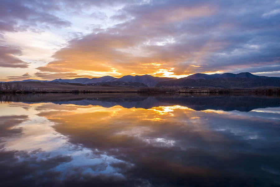 Colorado Insurance - Beautiful Purple and Gold Sunset Reflects off of a Lake With the Rocky Mountains Rising in the Distance