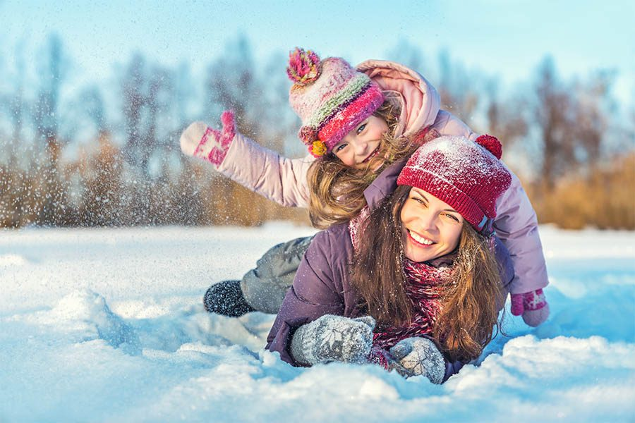 Personal Insurance - Mother and Daughter in Snow Gear Smile and Roll in the Snow, Young Daughter Tossing Powdery Snow Into the Air