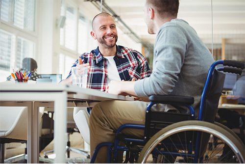 About Us - 1963 Man in Wheelchair Sitting with Friend in Office