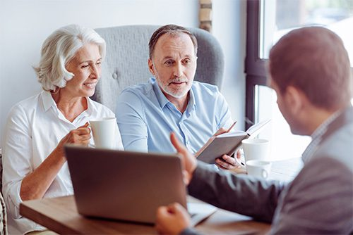 About Us - 1994 Older Couple Talking with Man at Desk with Laptop