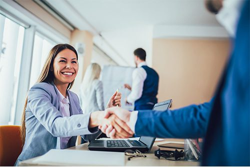 About Us - 2019 Professionally Dressed Woman Shaking Hands with Man at Desk in the Office