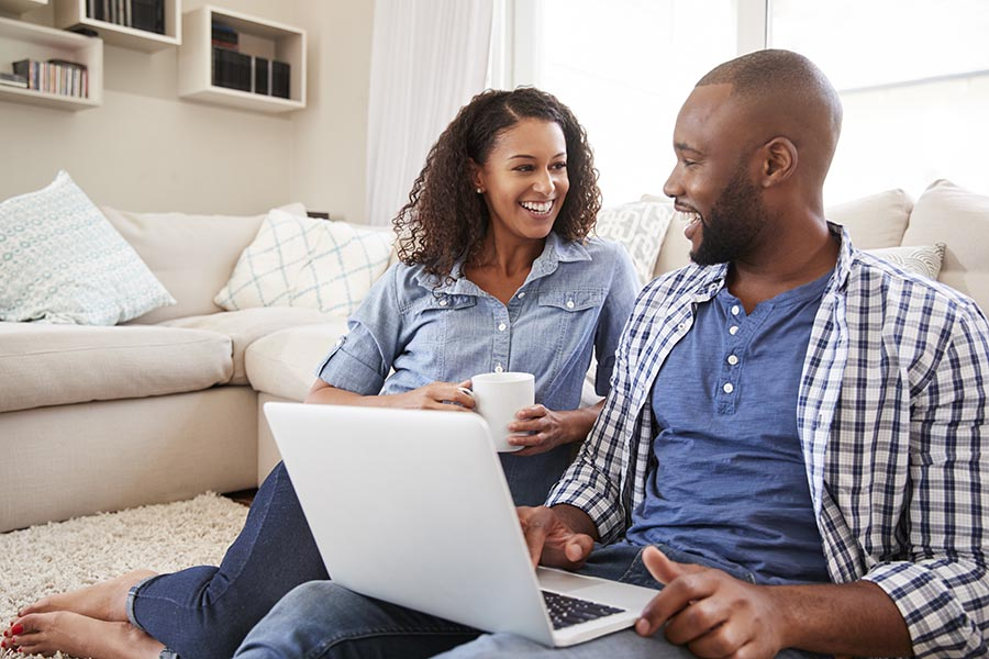 Blog - Young Couple Smiles as They Use a Laptop While Sitting on Their Living Room Floor, Nice White Couch and Bookshelves Behind Them