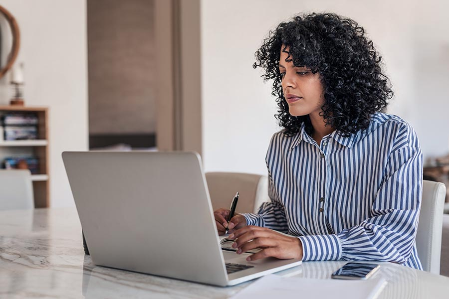 Client Center - Young Woman in Business Shirt Takes Notes While Reading on a Laptop at Her Kitchen Table