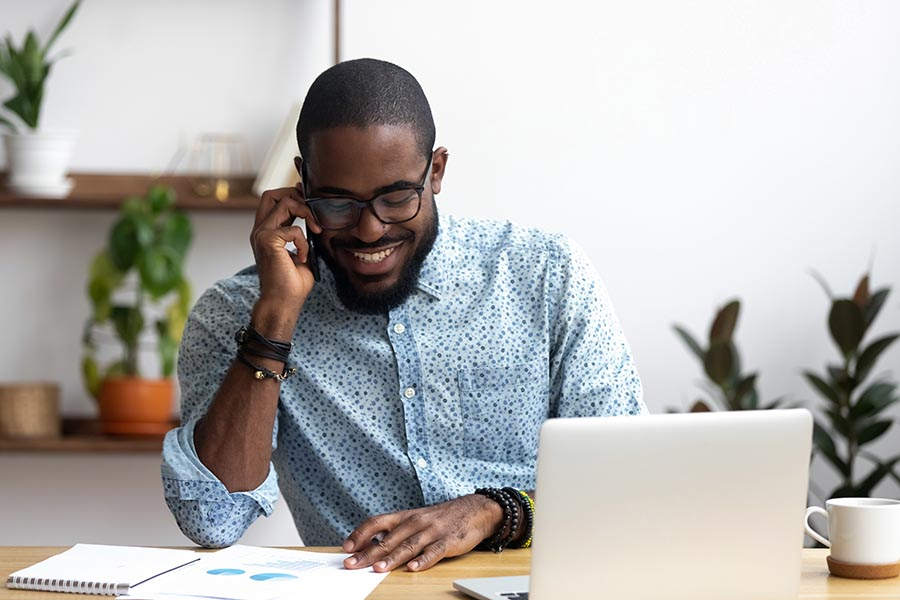 Contact Us - Young Man in Button-Down Shirt and Beaded Bracelets Smiles on a Call With Charts and a Laptop on His Desk, Coffee and Houseplants Nearby