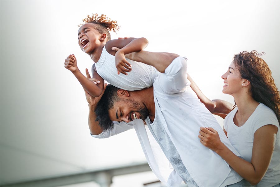 Personal Insurance - Young Girl Laughs as She Rides on Her Father's Shoulders and They Begin to Fall, Mother Smiling and Helping to Catch Them.jpg