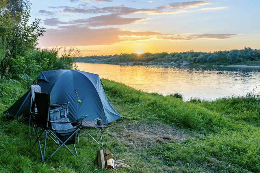 About Our Agency - Blue Camping Tent Set Up On Forest Edge Along A Still River With A Golden Sun Setting On The Horizon