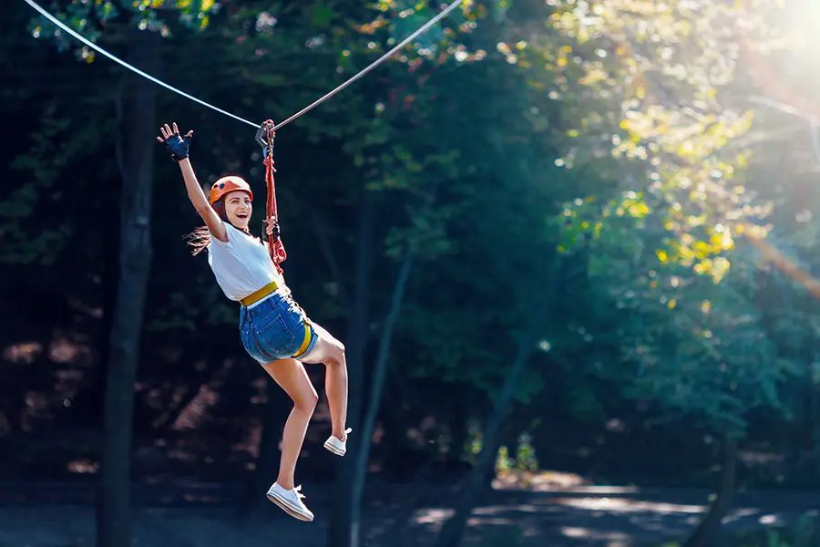 Adventure and Entertainment Insurance Cheerful Woman Waves as She is Gliding Along a Zipline in an Adventure Park